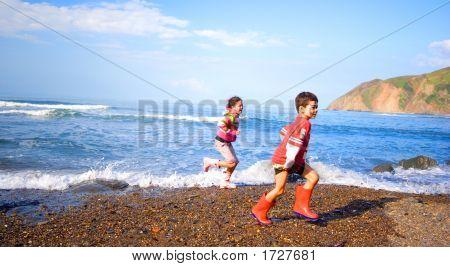 Niños y niñas a lo largo de la playa de olas