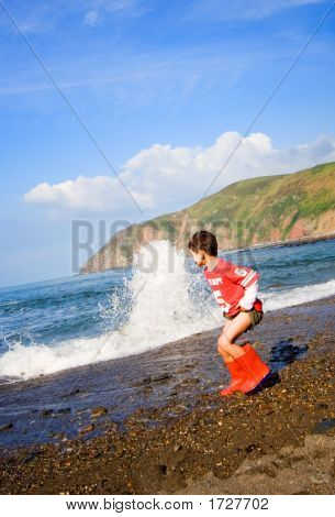 Waves Rolling Towards Young Boy On Beach