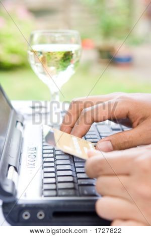 Hands Holding Credit Card By Computer Keyboard Outdoors