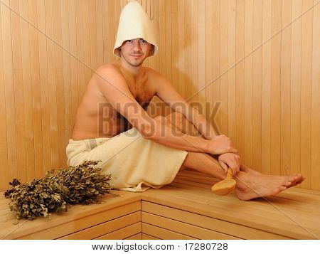 Young Handsome Man In A Towel Relaxing In A Russian Wooden Sauna