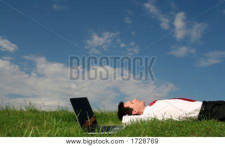 Empresario tumbado en la hierba con el ordenador portátil