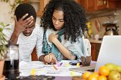 Young African-american Couple With Many Debts Calculating Gas And Electricity Bills While Doing Pape poster