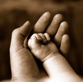 foto of sleeping baby  - Sepia of father supporting the fist of sleeping baby - JPG
