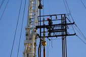 pic of roustabouts  - Roustabout works on high platform of oil drilling rig Kern County California - JPG