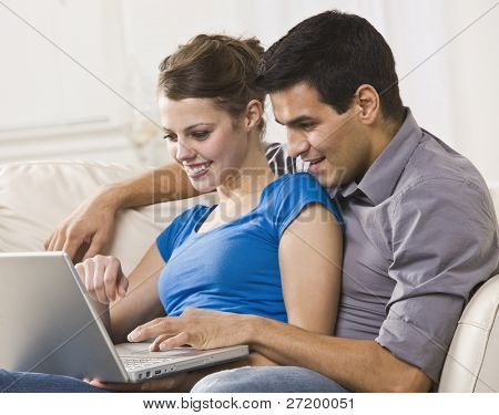 Attractive couple sitting together on a sofa and working on a laptop together. Horizontally framed photo.