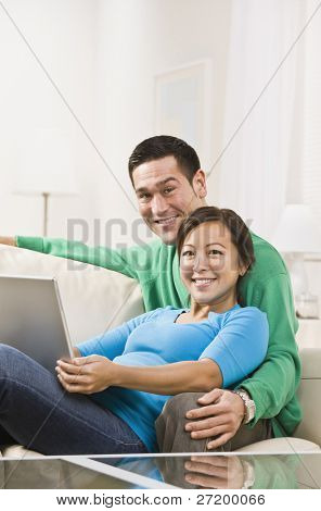 An attractive young couple sitting on a couch together and holding a laptop.  They are smiling at the camera. Vertically framed shot.