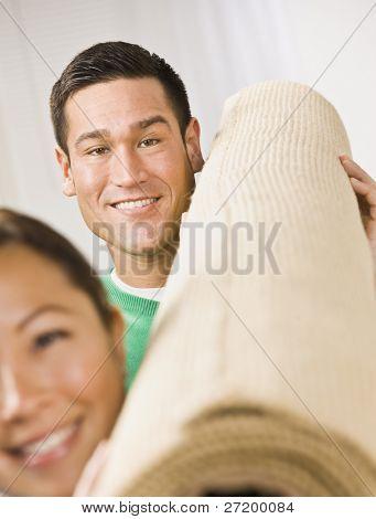eine attraktive young Couple holding eine Rolle des Teppichs. Sie Lächeln in die Kamera. vertikal fra