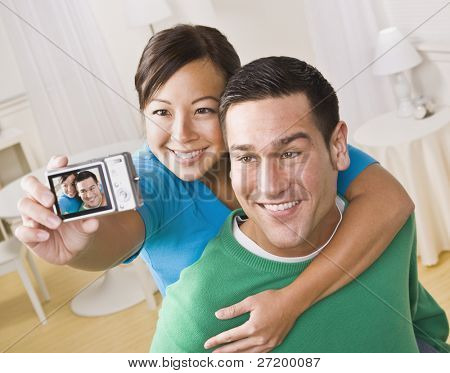 An attractive young couple taking their own picture with a digital camera. They are smiling.  The female is holding the camera. Horizontally framed shot.
