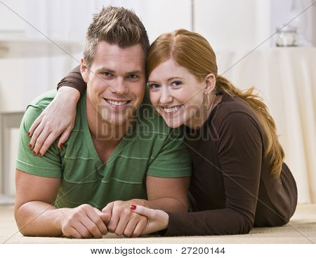 A young and attractive couple lying down together on their apartment floor.  They are relaxing on their stomachs and are smiling at the camera.  Horizontally framed photo.
