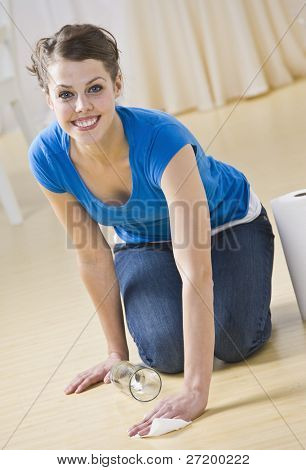 A young woman crouching down and using paper towels to clean up a spilled drink.  She is smiling and is facing the camera. Vertically framed shot.