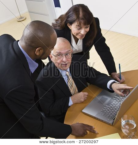 A group of business people are working on a laptop.  The elderly man is speaking to and looking at the younger man, and the young woman is looking at the computer screen.  Square framed shot.
