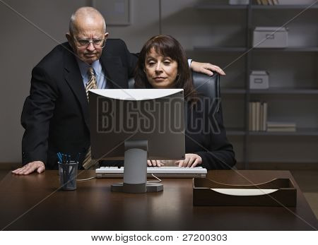 An elderly businessman and businesswoman are working together on a computer.  They are looking away from the camera.  Horizontally framed shot.