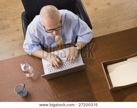 An elderly man is seated at a desk and is working on a laptop.  He is looking away from the camera.  Horizontally framed shot.