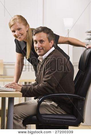 A businessman and woman are working together in an office.  They are smiling at the camera.  Vertically framed shot.