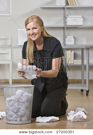A businesswoman is kneeling at a trash can in an office and is putting all of the paper off the floor into it.  She is smiling at the camera.  Vertically framed shot.