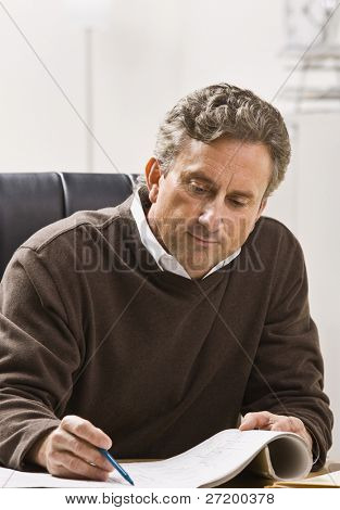 A businessman is sitting at his desk and working on some blueprints.  He is looking away from the camera.  Vertically framed shot.