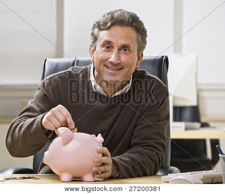 A man is seated at a desk in an office and is putting a coin into a piggy bank.  He is smiling at the camera.  Horizontally framed shot.