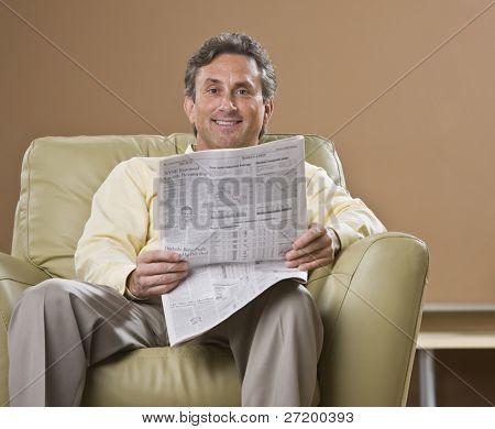 An older man is sitting in a chair and reading a newspaper.  He is smiling at the camera.  Horizontally framed shot.