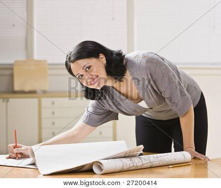 Attractive woman leaning over desk with drawings. Pen in hand, looking at camera. Horizontal.