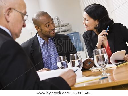 Three attractive business people sitting at a table with water and paperwork. Horizontal