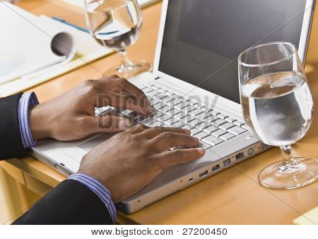 afrikakarte american männlich Hands typing on Laptop-Tastatur. Glas Wasser auf Schreibtisch. horizontale