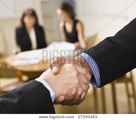 Mixed race handshake with two woman in background. Horizontal