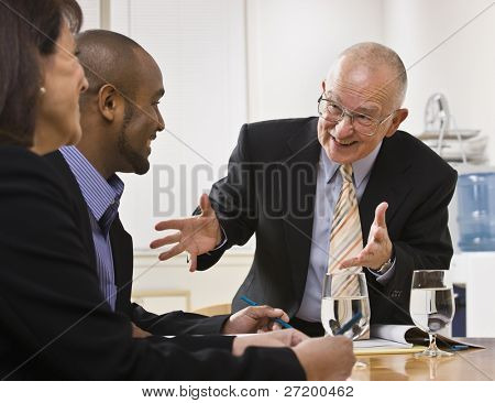 Business team meeting with two men and a woman sitting at a desk with water.  Horizontal
