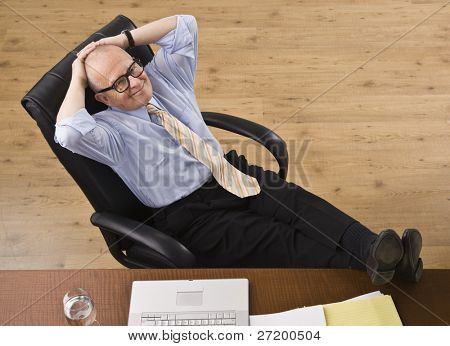 Attractive senior business man relaxing with feet on desk, reclining in chair, smiling at camera. Horizontal