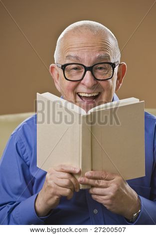 Laughing senior male reading a book on a couch. Vertical