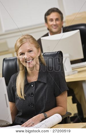 Attractive business people sitting at desks. Woman in front, man behind. Smiling at the camera. Vertical