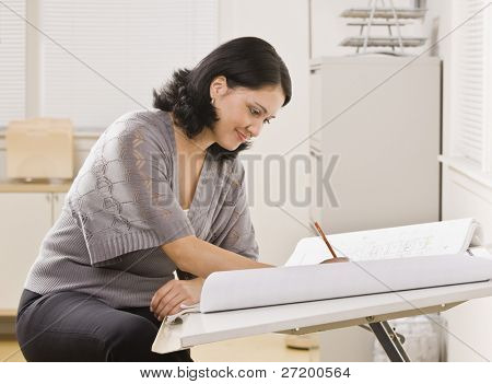 A young woman is sitting at a desk in an office and is working on blueprints.  She is looking away from the camera.  Horizontally framed shot.
