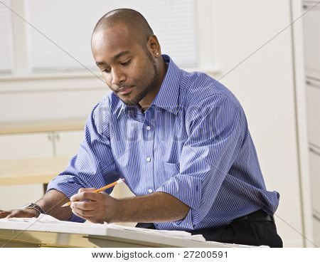 A young businessman is working on some blueprints in an office.  He is looking away from the camera.  Horizontally framed shot.