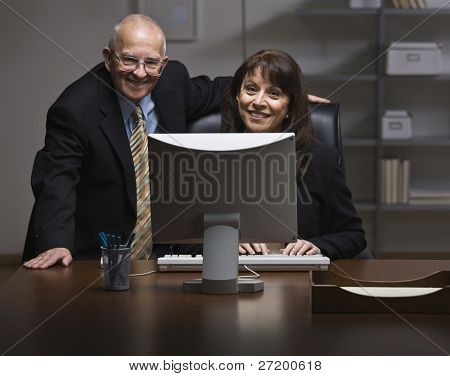 An elderly businessman and a younger businesswoman are working together on a computer in an office.  They are smiling at the camera.  Horizontally framed shot.