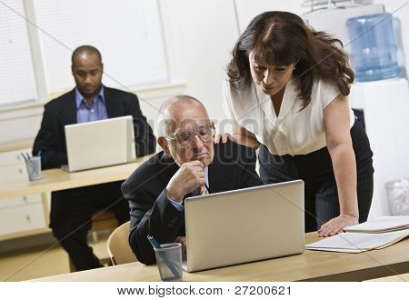 A group of business people are in an office and are working on computers.  They are looking away from the camera.  Horizontally framed shot.