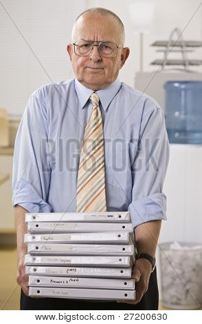 An elderly businessman is holding a stack of binders.  He is looking at the camera.  Vertically framed shot.
