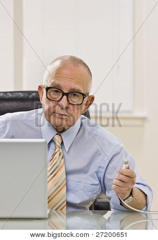 An elderly man is working on a computer in an office.  He is looking at the camera.  Vertically framed shot.