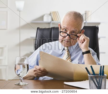 An elderly man is looking at a file in an office.  Horizontally framed shot.