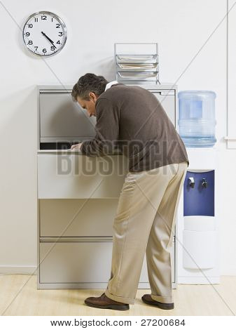 A businessman is looking through a drawer at an office.  Vertically framed shot.