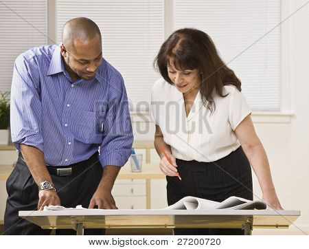 A businessman and woman are working together in an office.  They are looking away from the camera.  Horizontally framed shot.