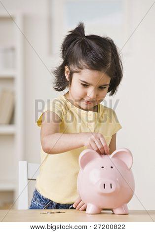 ein junges Mädchen spielt mit einem Sparschwein. Sie sucht von der Kamera entfernt. vertikal gerahmt