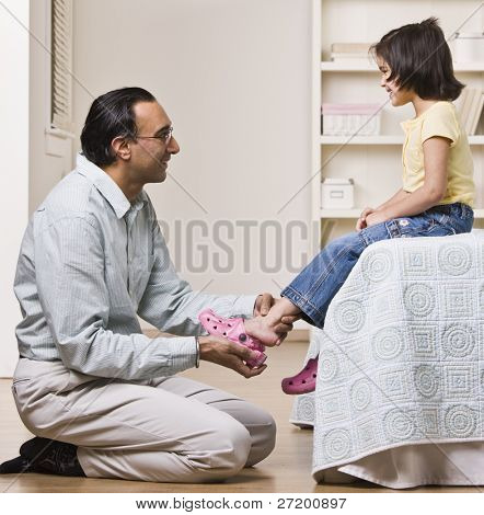 A father is helping his baby daughter with her shoes.  They are smiling and looking each other.  Square framed shot.