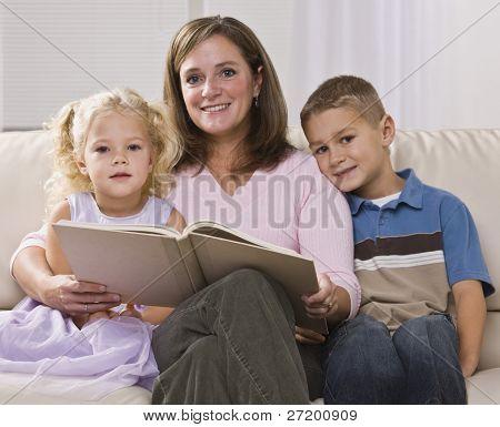 eine Mutter ist, ihre zwei kleinen Kindern lesen. Sie sind alle Lächeln in die Kamera. quadratische gerahmte s