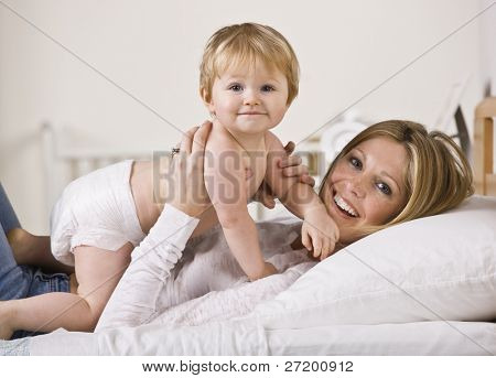 A young mother is holding her baby daughter above her.  They are both smiling at the camera.  Horizontally framed shot.