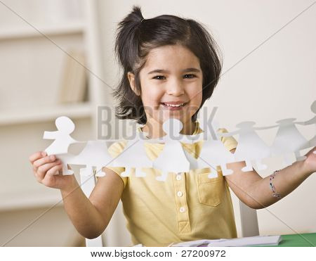 A young girl is seated at a desk and is holding up paper dolls.  She is smiling at the camera.  Horizontally framed shot.
