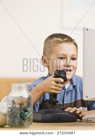 a young boy is playing computer games.  He is smiling and looking at the screen.  Vertically framed shot.
