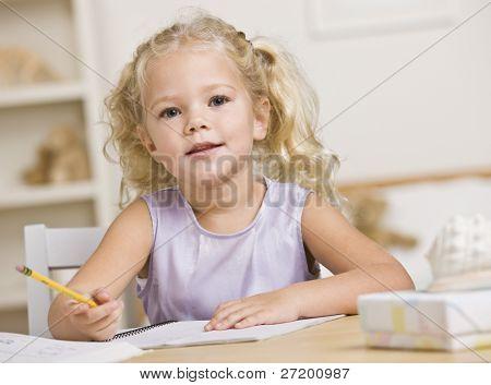 ein junges Mädchen sitzt an einem Tisch und Färbung in Büchern. Sie sucht in die Kamera. horizontale