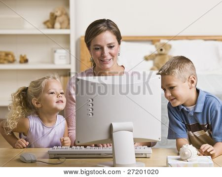 A mother and her two children are playing together on a computer.  They are smiling and lookign at the screen.  Horizontally framed shot.