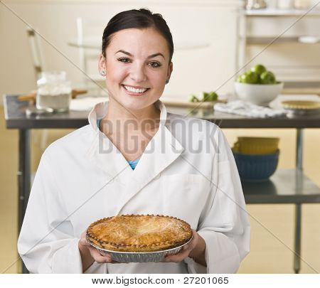 A young woman is holding a pie in a kitchen.  She is smiling at the camera.  Horizontally framed shot.