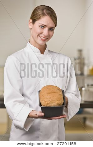 A young woman is standing in a kitchen and holding out a loaf of bread.  She is smiling at the camera.  Vertically framed shot.