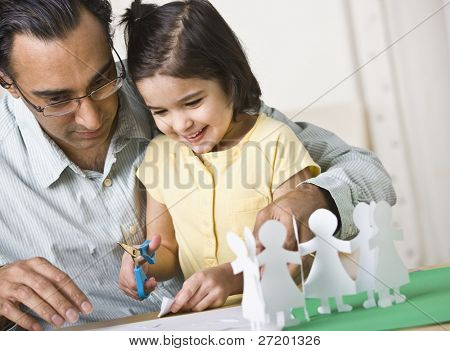 A father playing with his daughter.  He is helping her cut out paper dolls and she is smiling.  Horizontally framed shot.
